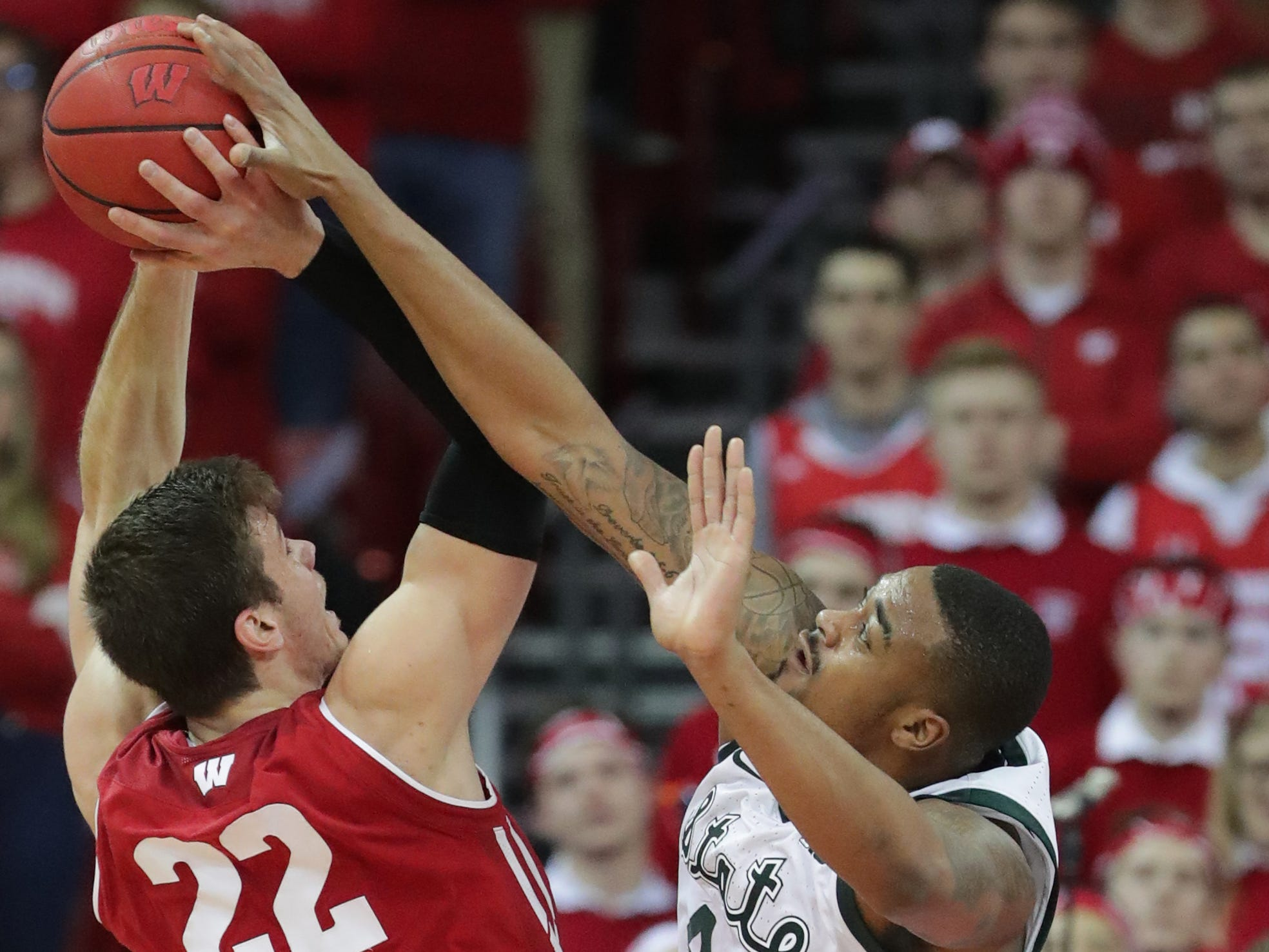 Wisconsin forward Ethan Happ tries to get a shot off over Michigan State forward Nick Ward.