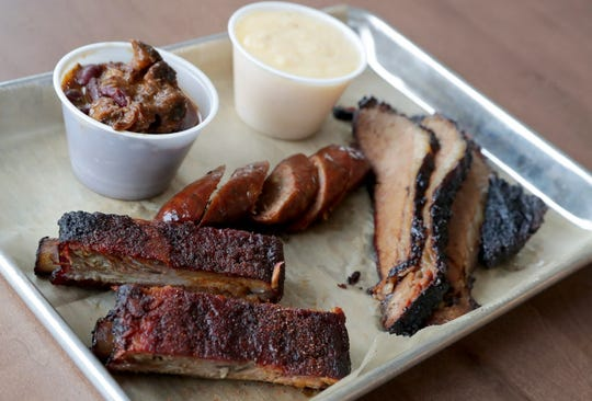 Customers can create their own combos at Heaven's Table BBQ at Crossroads Collective. This one of three meats and two sides includes ribs, sausage, brisket, meaty baked beans and grits.