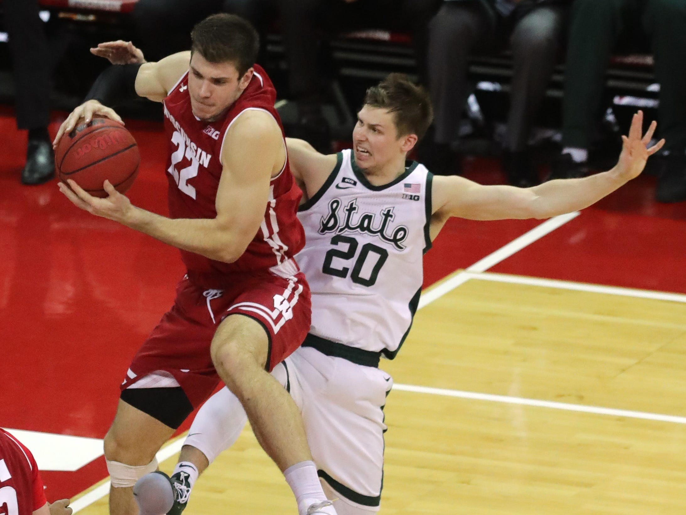 Wisconsin forward Ethan Happ  pulls in a rebound in front of  Michigan State guard Matt McQuaid.