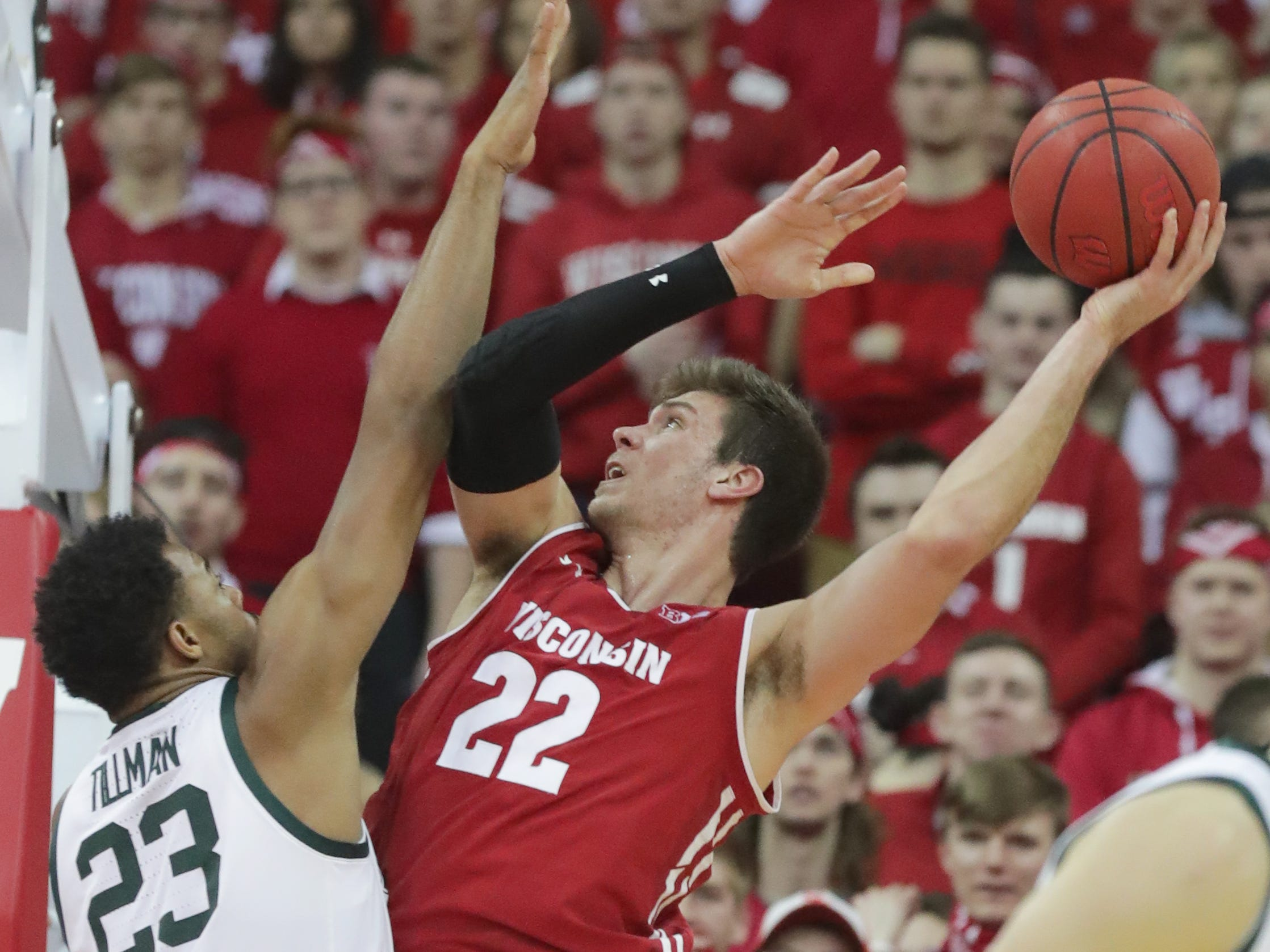 Wisconsin forward Ethan Happ scores over  Michigan State forward Xavier Tillman on Tuesday night.