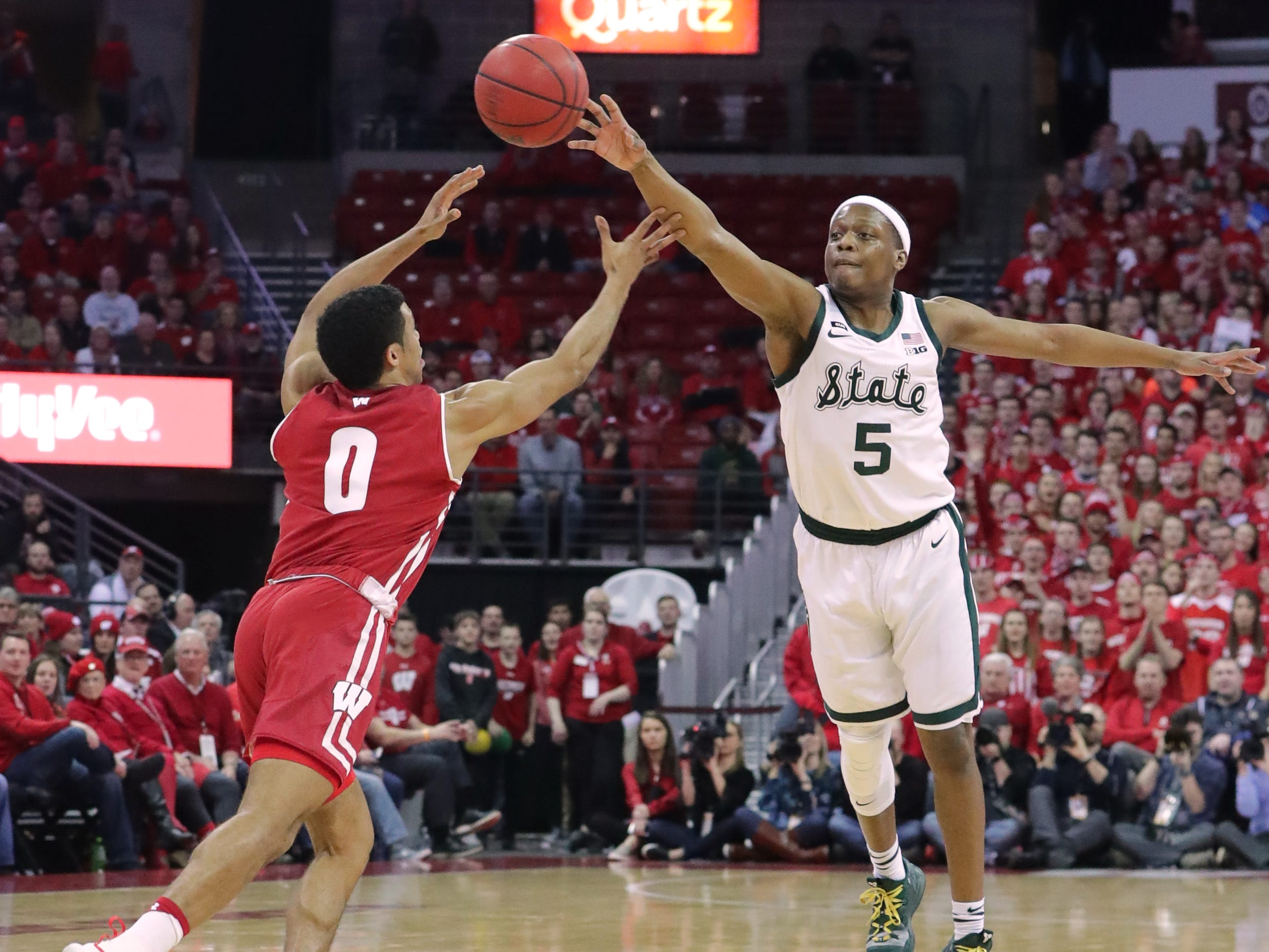 Michigan State guard Cassius Winston beats Wisconsin guard D'Mitrik Trice to a loose ball on Tuesday night.