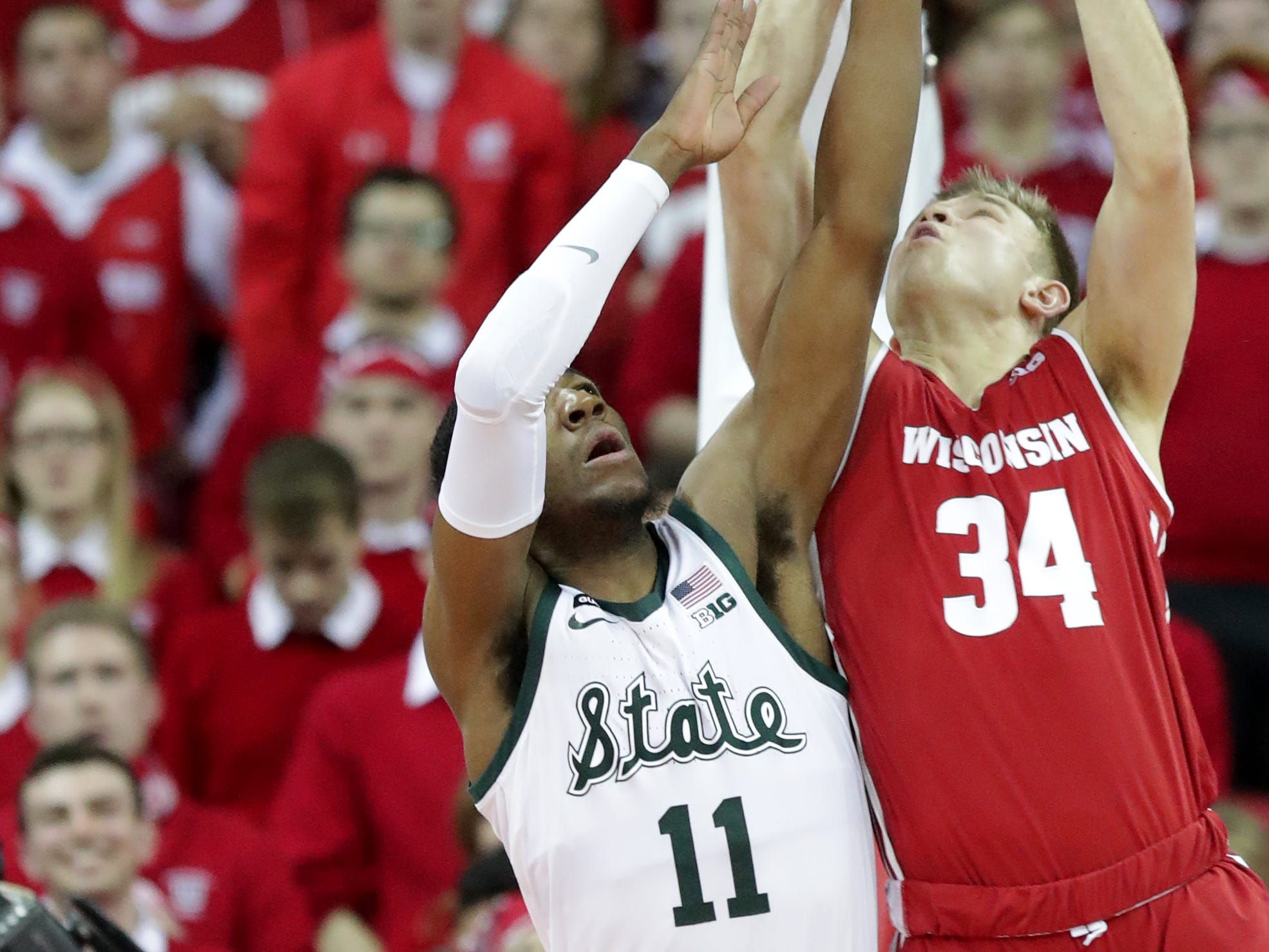Wisconsin guard Brad Davison scores despite the efforts of  Michigan State forward Aaron Henry.