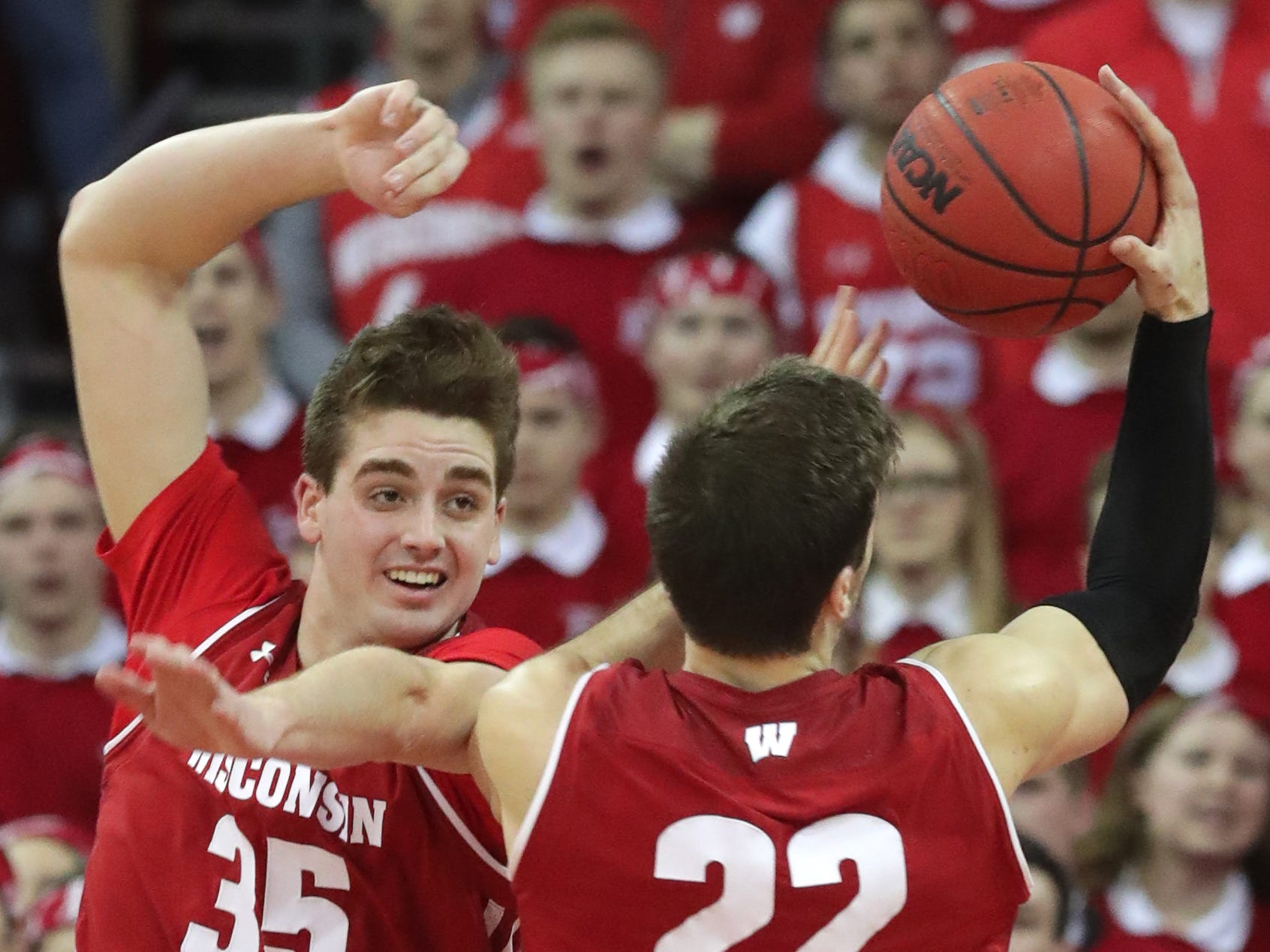 Wisconsin forward Nate Reuvers directs a rebound to forward Ethan Happ.