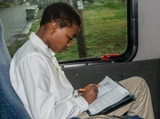 A Valiant Cross Academy student does school work on the Rev. Ken Austin's church bus Tuesday morning, Feb. 12, 2019. Austin drives a church bus throughout the school week to transport Montgomery children to and from Valiant Cross Academy.