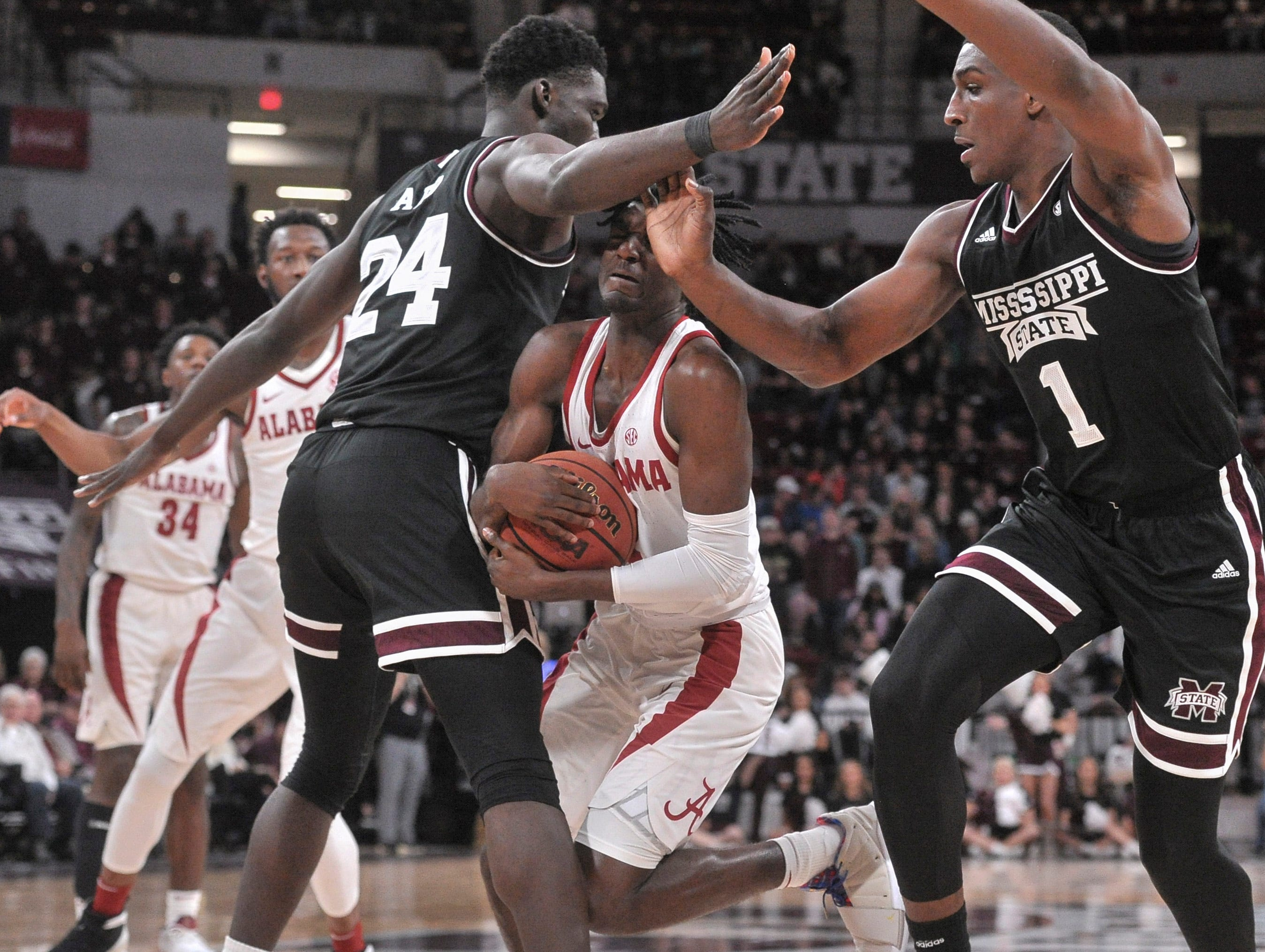 Feb 12, 2019; Starkville, MS, USA; Alabama Crimson Tide guard Kira Lewis Jr. (2) controls the ball between Mississippi State Bulldogs forward Abdul Ado (24) and State Bulldogs forward Reggie Perry (1) during the second half at Humphrey Coliseum. Mandatory Credit: Justin Ford-USA TODAY Sports