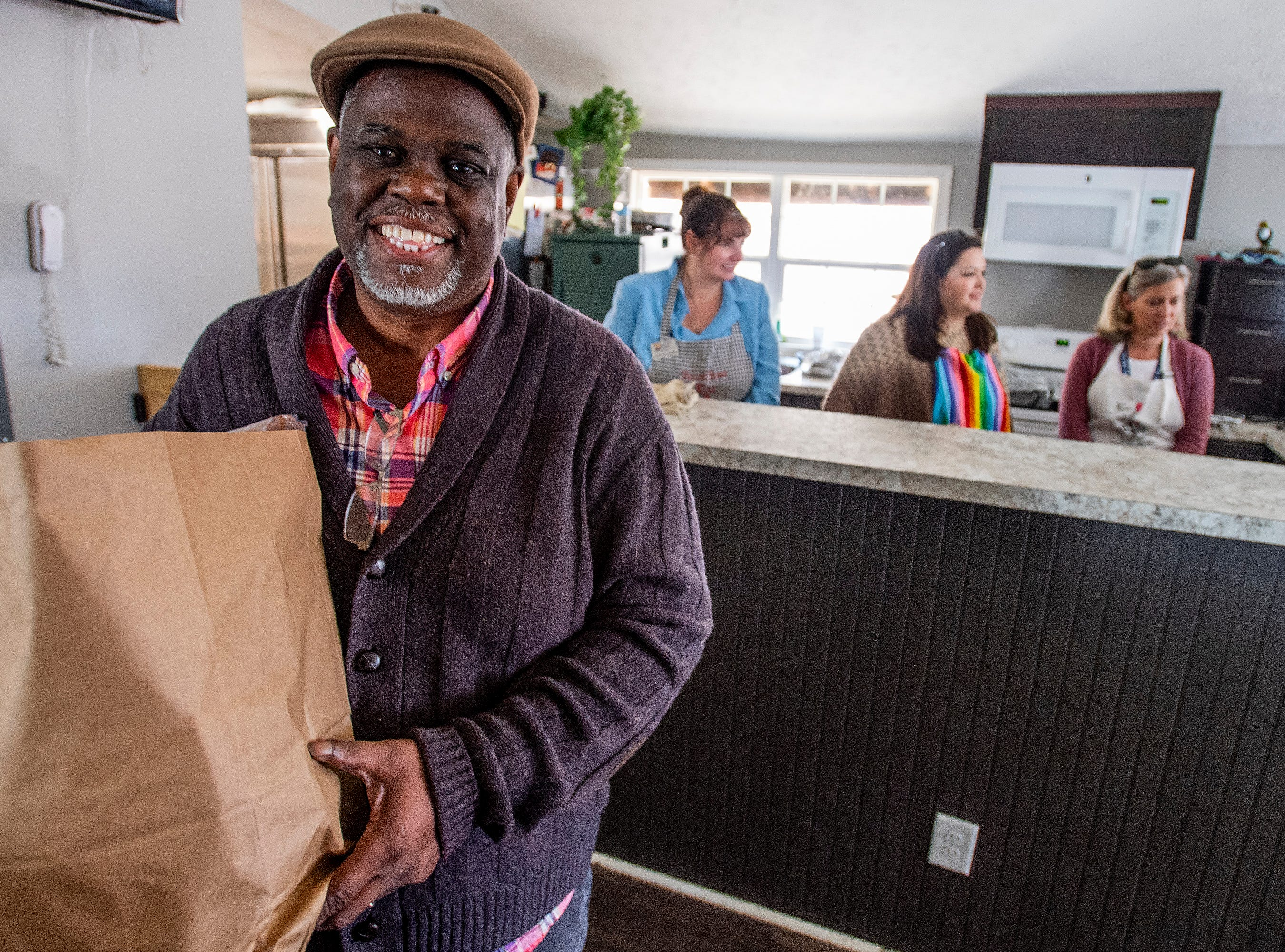 Ken Austin, executive director of the Mercy House and pastor at New Walk of Life Church, helps hand out groceries at Mercy House in Montgomery, Ala., on Wednesday February 13, 2019.