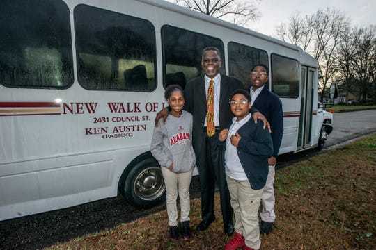 The Rev. Ken Austin with his children outside of the church bus he uses to transport Montgomery youths to Valiant Cross Academy on Tuesday, Feb. 12, 2019.