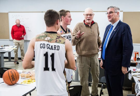 Gov. Eric Holcomb speaks Blackford coach Jerry Hoover, center, and players Brandon Stroble and Caleb Mealy (11) before their game against Daleville at Blackford High School Tuesday, Feb. 12, 2019.