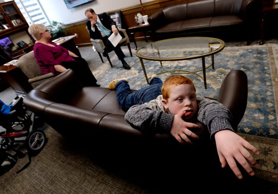 Hatcher Ryan, 10, who has Down syndrome, rests on a couch as single mother Jennifer Schultz talks with Tennessee State Senate Majority Leader Jack Johnson, R-Franklin, in his office during Disability Day on the Hill Tuesday, Feb. 12, 2019, in Nashville, Tenn. Families and advocates of people with disabilities in Tennessee met with lawmakers to express concerns and the needs of the disabled in the state.