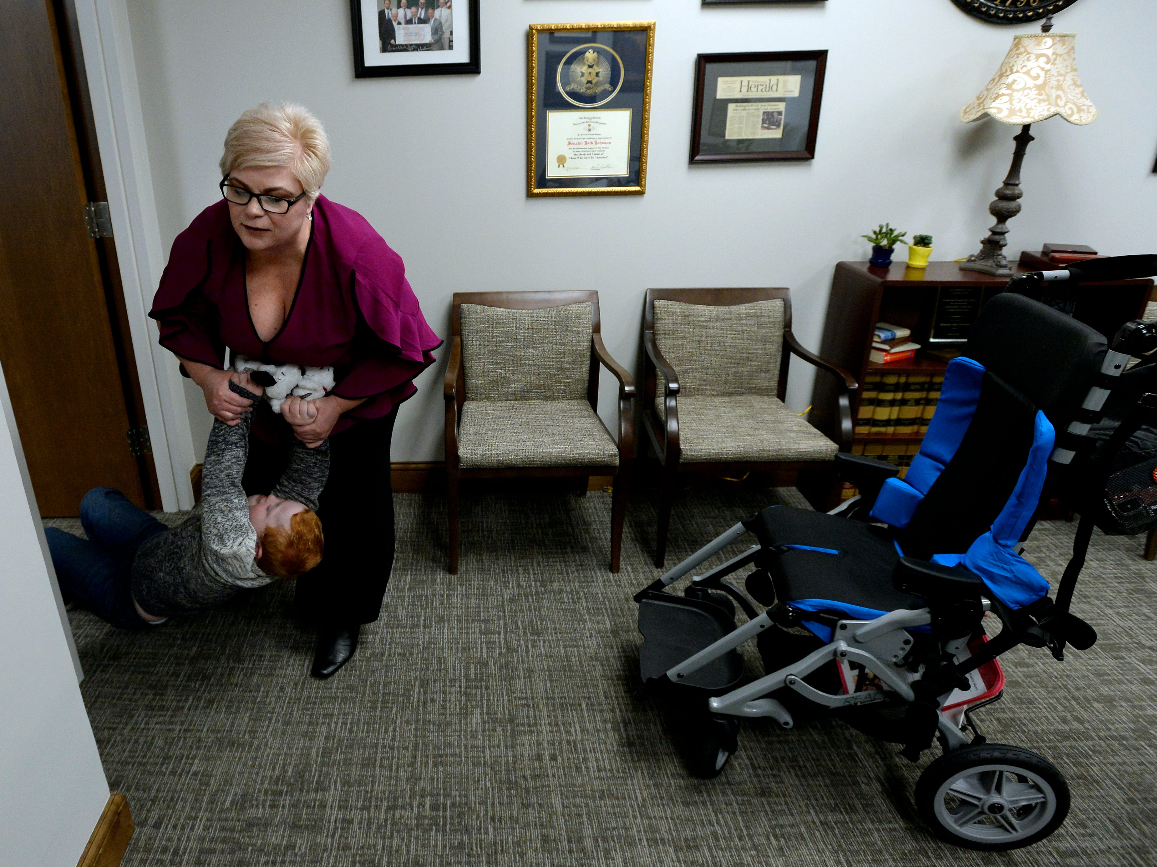 Single mother Jennifer Schultz struggles to stop her son Hatcher Ryan, 10, who has Down syndrome, from crawling into the office of Tennessee State Senate Majority Leader Jack Johnson before she speaks  with him during Disability Day on the Hill Tuesday, Feb. 12, 2019, in Nashville, Tenn. Families and advocates of people with disabilities in Tennessee met with lawmakers to express concerns and the needs of the disabled in the state.
