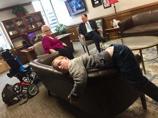 Ten-year-old Hatcher Ryan, exhausted after a morning advocating on the Hill, rests in the office of Sen. Jack Johnson, R-Franklin. Behind him, his mom, Jennifer Schultz, talks to Johnson about her challenges raising a son with disabilities and her hope that Tennessee will create a Medicaid pathway for families like hers with a Katie Beckett or TEFRA program.