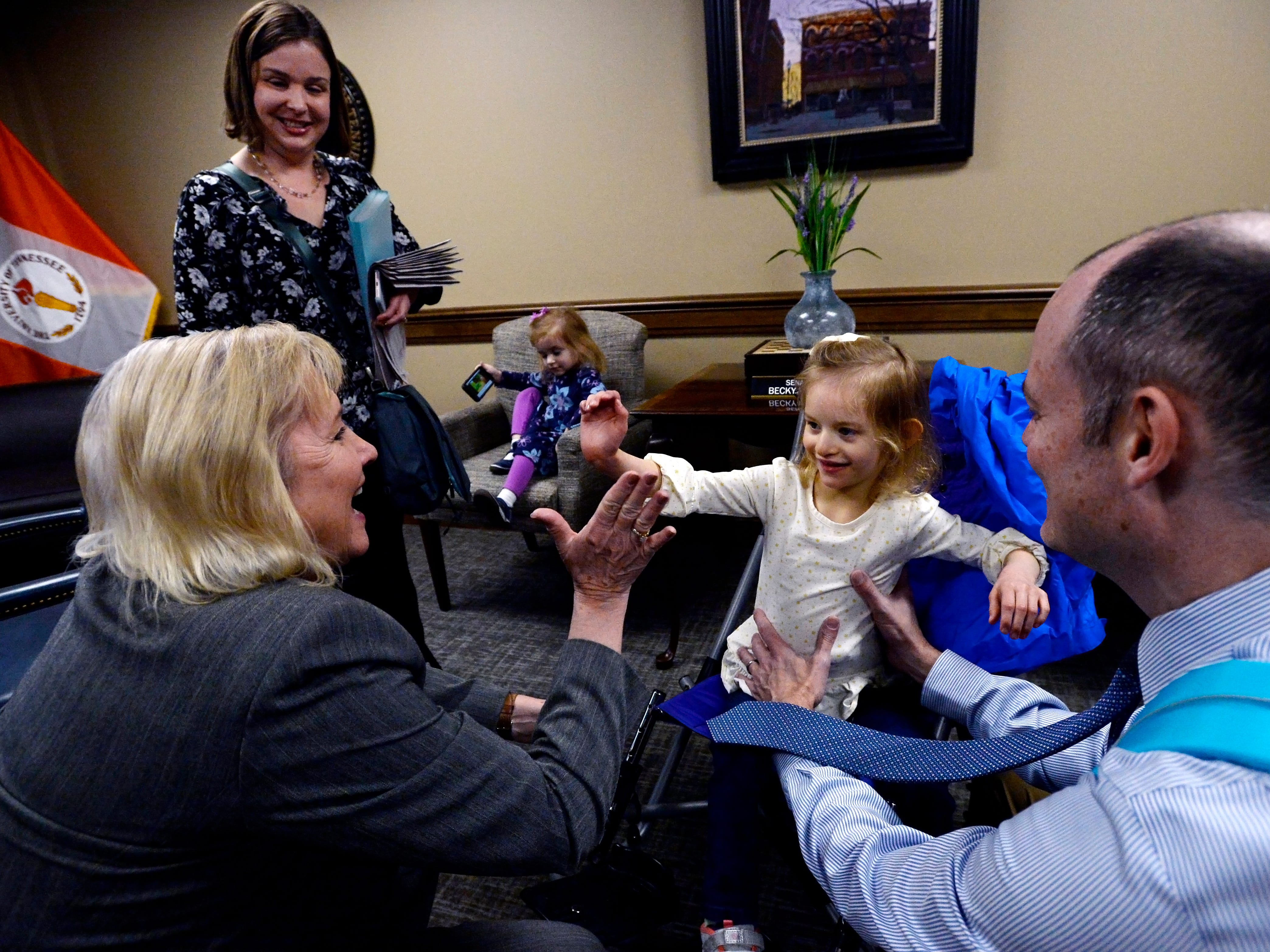 Claire Fox, 4, high-fives state Sen. Becky Duncan Massey, R-Knoxville, before her parents, Jessica, left, and Sean Fox, talk with the lawmaker during Disability Day on the Hill on Tuesday, Feb. 12, 2019, in Nashville.