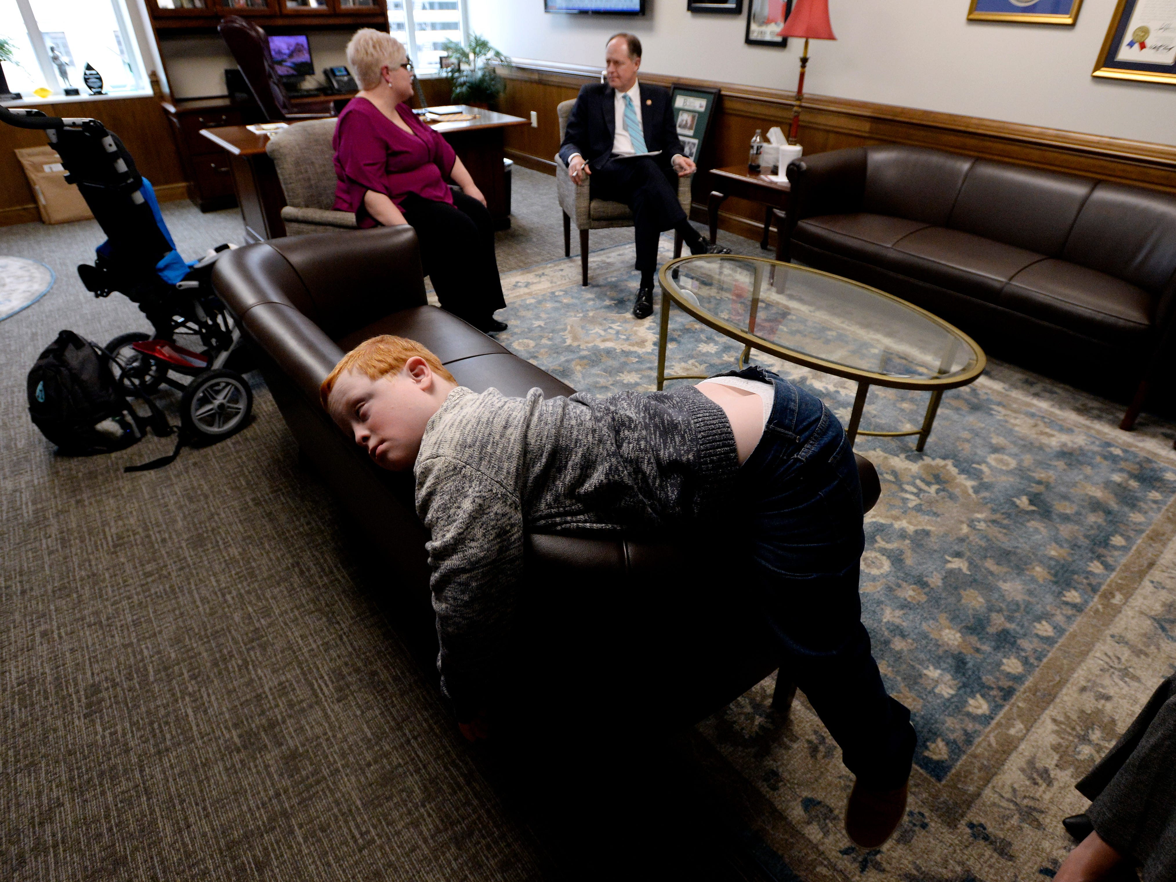 Hatcher Ryan, 10, who has Down syndrome, rests on a couch as single mother Jennifer Schultz speaks with  Tennessee State Senate Majority Leader Jack Johnson, R-Franklin, in his office during Disability Day on the Hill Tuesday, Feb. 12, 2019, in Nashville, Tenn. Families and advocates of people with disabilities in Tennessee met with lawmakers to express concerns and the needs of the disabled in the state.
