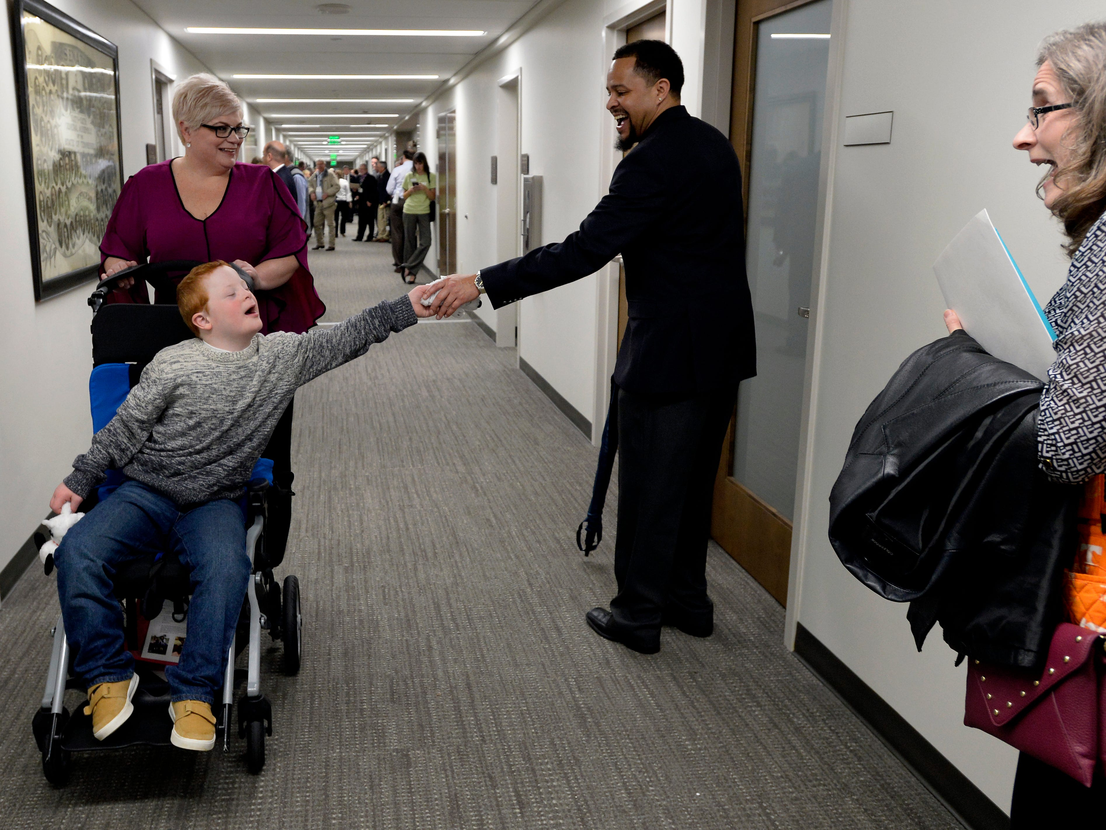 Hatcher Ryan, 10, who has Down Syndrome, shakes hands with people in the hallway of the Cordell Hull building as his mother Jennifer Schultz follows behind before she visits with Tennessee State Senate Majority Leader Jack Johnson during Disability Day on the Hill Tuesday, Feb. 12, 2019, in Nashville, Tenn. Families and advocates of people with disabilities in Tennessee met with lawmakers to express concerns and the needs of the disabled in the state.