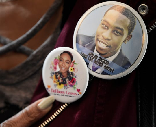 Shirl Baker wears buttons on her label honoring her daughter, DeEbony Groves, and fellow Waffle House victim, Akilah Dasilva, after Travis Reinking pleaded not guilty to charges related to a mass shooting that killed four people and injured several others at a Waffle House in 2018.
