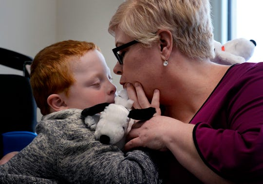 Single mother Jennifer Schultz kisses her son, Hatcher Ryan, 10, who has Down syndrome, as they wait to speak with state senators during Disability Day on the Hill on Tuesday, Feb. 12, 2019, in Nashville.