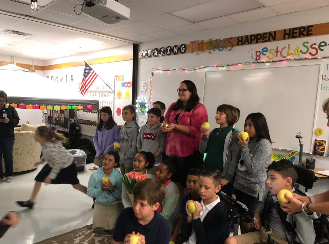 """Krista Fusco, a 4th grade teacher at Vineyards Elementary, receives the first Golden Apple award on Wednesday, Feb. 13, 2019. Fusco, 33, always tells her class that it's OK to make mistakes and wants them to have fun in school. Today they were detectives investigating """"crime scenes"""" scattered around the classroom. """"If they're not laughing, they're not learning,"""" she said."""