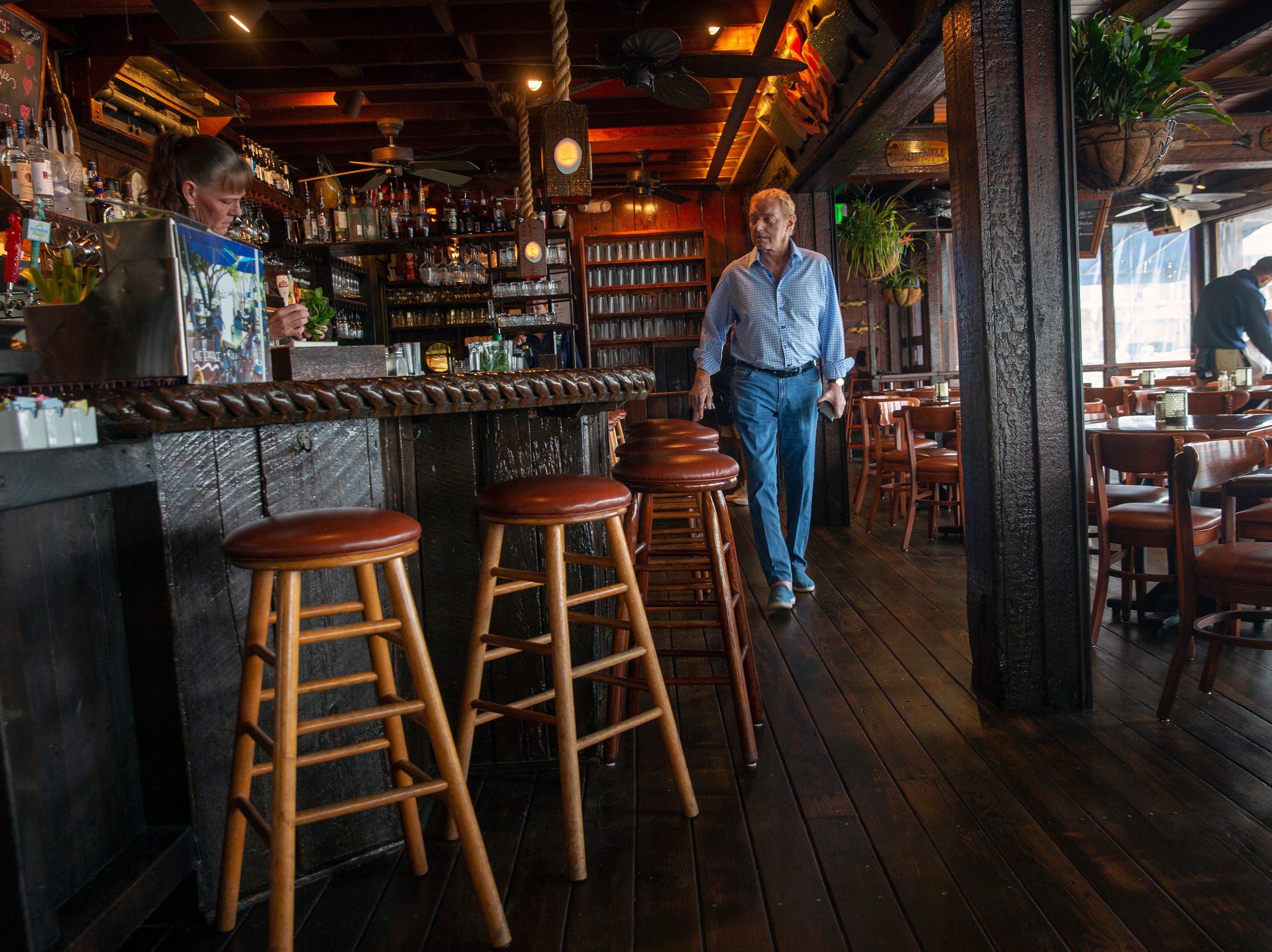 Vin Depasquale, the former owner of The Dock restaurant walks along the restaurant's bar, Wednesday, Feb. 13, 2019, at The Dock restaurant in Naples.