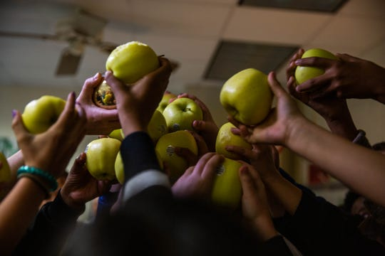 Ashley Stafford's students hold up their apples in celebration after Stafford won a Golden Apple award at Lake Park Elementary School in Naples on February 13, 2019. Real apples were distributed to each classroom as teachers received their awards.