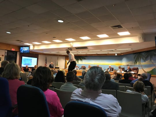 A Naples resident jumps on a chair during the Naples planning board meeting on Feb. 13, 2019 to make a point about how the Naples Beach Hotel developer is misconstruing the height of the proposed mid-rise condo buildings. A standing-room-only crowd was on hand as the board began its review of a proposal to tear down the Naples Beach Hotel and build a smaller resort and add residential condominiums in its place.