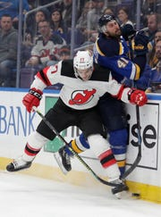 New Jersey Devils Kenny Agostino slams St. Louis Blues' Robert Bortuzzo (41) into the boards as he chases the puck in the first period of an NHL hockey game, Tuesday, Feb. 12, 2019, in St. Louis.