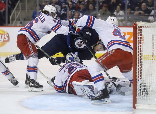 Winnipeg Jets center Adam Lowry (17) is hit by New York Rangers right wing Mats Zuccarello (36) after trying to score on goaltender Henrik Lundqvist (30), as defenseman Neal Pionk (44) defends the crease during the second period of an NHL hockey game Tuesday, Feb. 12, 2019, in Winnipeg, Manitoba.