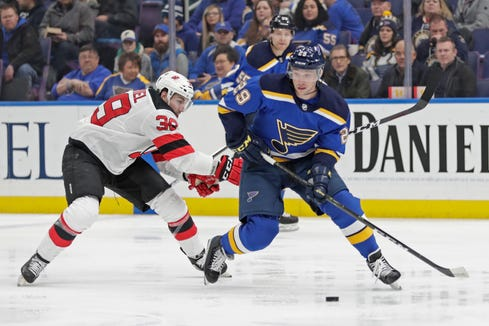 New Jersey Devils' Kurtis Gabriel (39) battles St. Louis Blues' Vince Dunn (29) for the loose puck in the first period of an NHL hockey game, Tuesday, Feb. 12, 2019, in St. Louis.