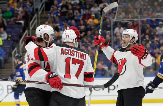 New Jersey Devils' Pavel Zacha, left, celebrates with teammates Kenny Agostino, center, and Nick Lappin, right, after scoring a goal in the first period of an NHL hockey game against the St. Louis Blues, Tuesday, Feb. 12, 2019, in St. Louis.