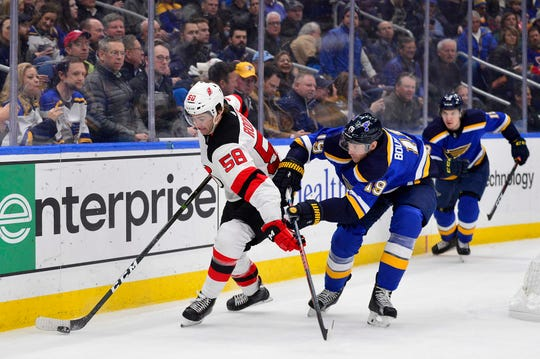 Feb 12, 2019; St. Louis, MO, USA; New Jersey Devils center Kevin Rooney (58) handles the puck as St. Louis Blues defenseman Jay Bouwmeester (19) defends during the second period at Enterprise Center.
