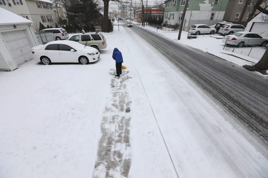 Victor Marquez shovels the sidewalk along Grand St. in Little Ferry, Tuesday, February 12, 2019.