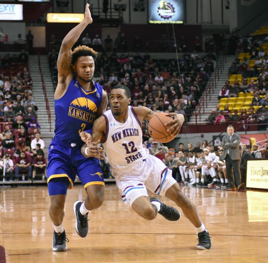 New Mexico State's AJ Harris drives to the rim with a Kansas City player draped over him.