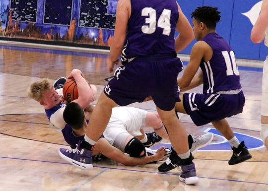 Carlsbad's Andrew Miller fights for a loose ball against Clovis' Anthony Guiterrez in the fourth quarter of Tuesday's game. Miller won possession and Carlsbad beat Clovis, 45-35.