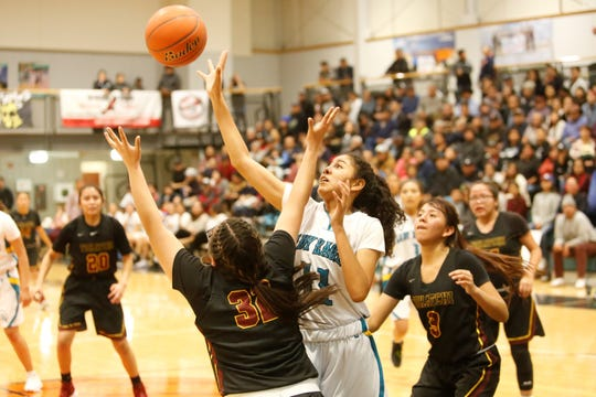 Navajo Prep's Hailey Martin tips the ball back out to the right edge of the wing against Tohatchi's Gabrielle Thomas (32) during Tuesday's District 1-3A game at the Eagles Nest in Farmington. Prep is No. 6 in this week's NMOTSC 3A girls rankings.