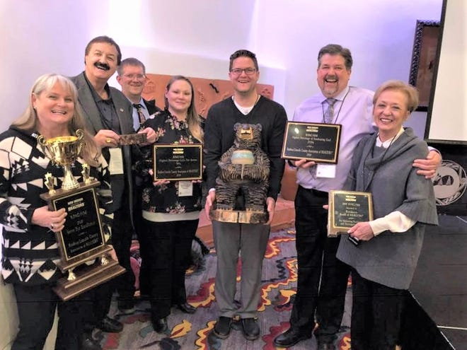 Receiving the Strive for Excellence Award from left are Mary Austin, Gary Lynch, James Russ II, Deena Turner, Sean Simpson, Troy Biggs and Cindy Lynch.