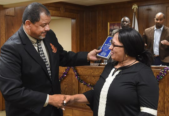 Mayor Julius Alsandor presents Mary Stephanie Richard with a plaque of appreciation after she was selected as employee of the month for the city of Opelousas.