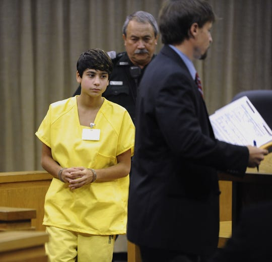 Elena Rendell steps forward to stand by the side of Assistant Public Defender Clint Davis as they appeared before Judge Nickolas Geeker on Sept. 29, 2011.