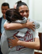 Anthony Borges, rear, who was shot during the Parkland, Fla., school shooting, hugs Marianne Sheehan after a news conference with Florida governor Ron DeSantis, Wednesday, Feb. 13, 2019, in Fort Lauderdale, Fla. DeSantis ordered a statewide grand jury investigation on school safety.