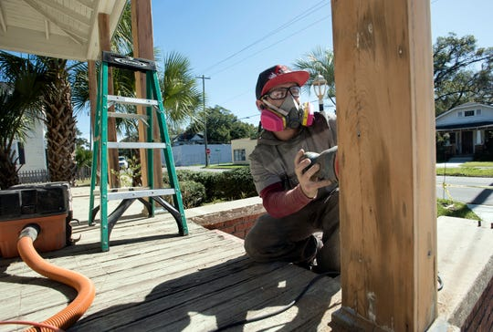 Michael Edward Stubbs Jr. works to renovate the exterior of a historic home on West Gregory Street in downtown Pensacola on Wednesday.