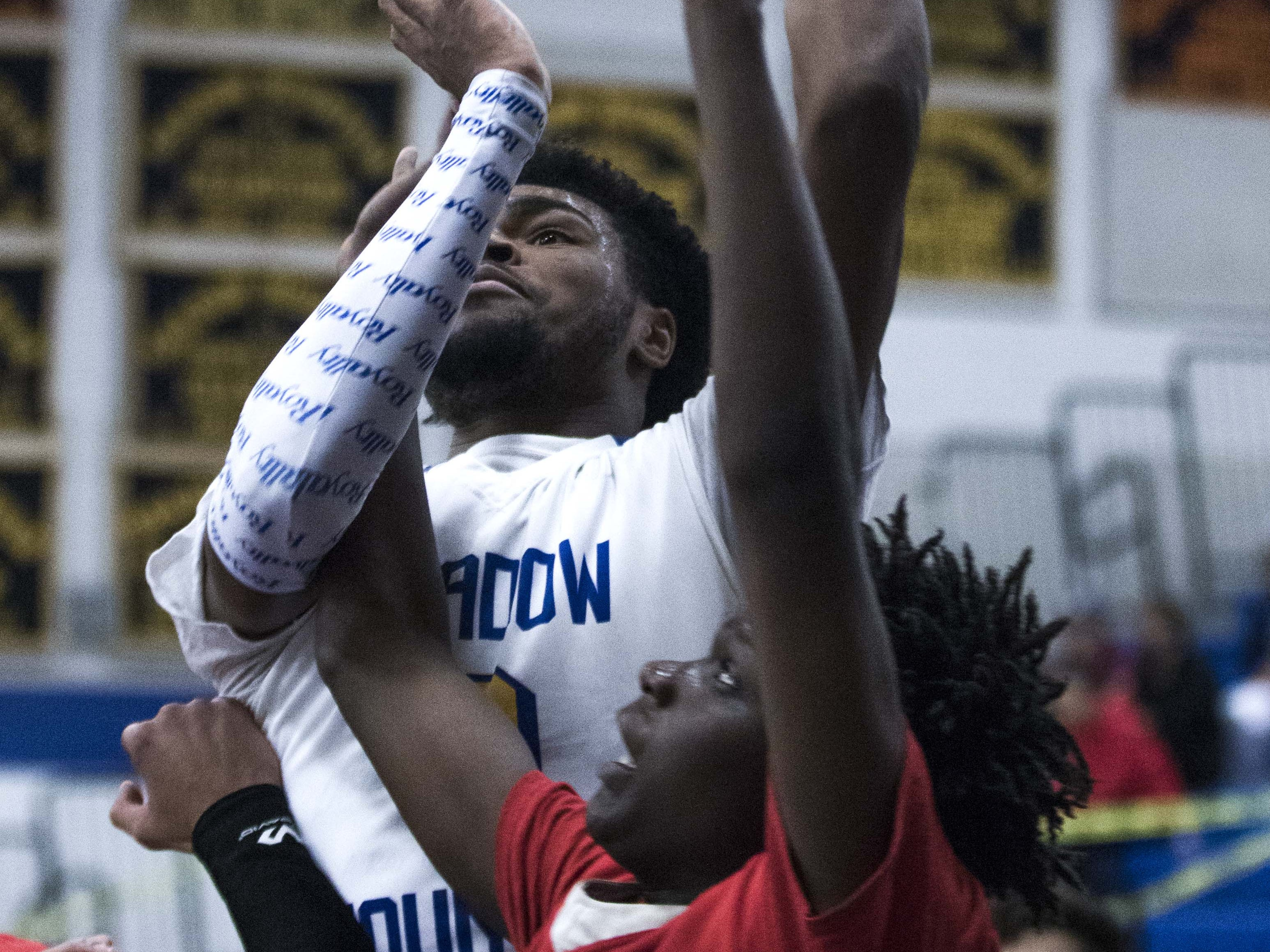 Shadow Mountain's Jalen Williams (0) goes up and over a Moon Valley player during the first half of their game in Phoenix, Tuesday, Feb .12,  2019.