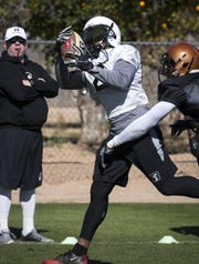 Jamal Miles (RB/WR) catches a pass during Rattlers practice, February 12, 2019, at Gene Autry Sports Complex, 4125 E McKellips Road, Mesa. Looking on is Coach Kevin Guy (left).
