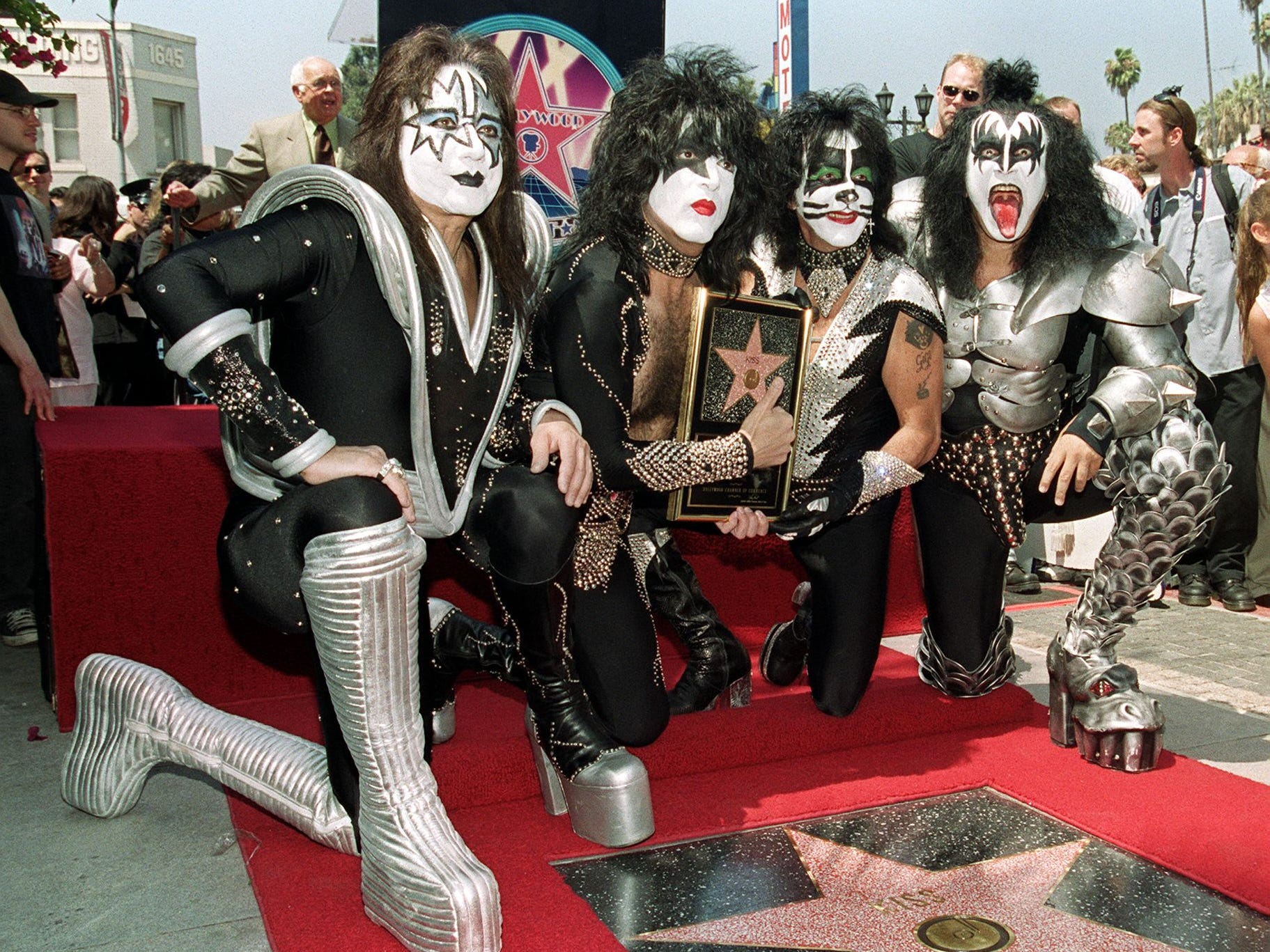 HOLLYWOOD:  Members of the rock band Kiss (from left to right): Ace Frehley, Paul Stanley, Peter Criss and Gene Simmons pose by the star they received during a Hollywood Walk of Fame ceremony on Aug. 11, 1999 in Hollywood, Ca.  The group, known for their theatrical stage performances, has sold 80 million records over their 26 year career. AFP PHOTO/Vince BUCCI