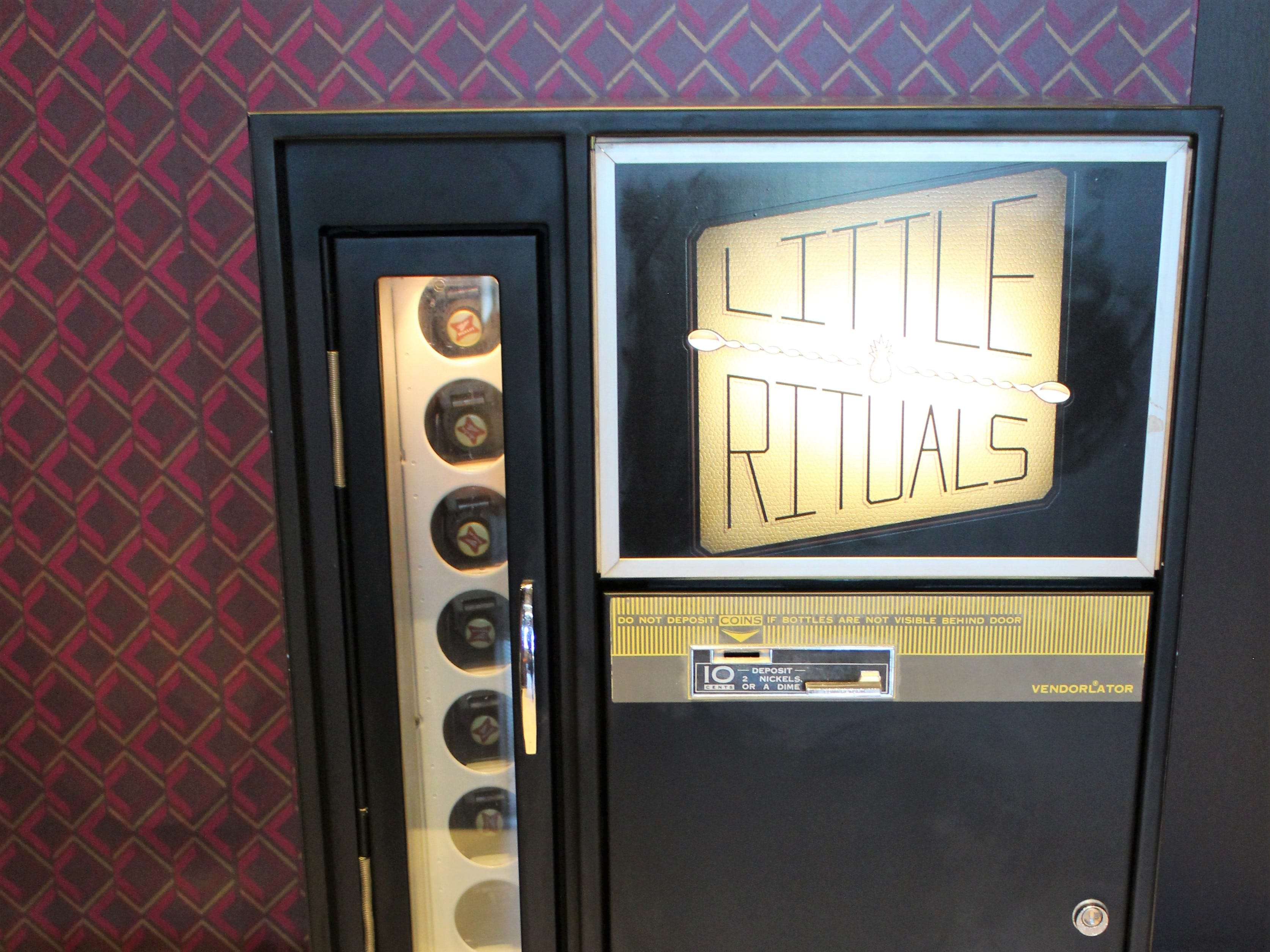 The lobby at Little Rituals, located inside the Courtyard by Marriott Phoenix Downtown, offers a retro-fitted soda vending machine that now dispenses glass bottles of beer.