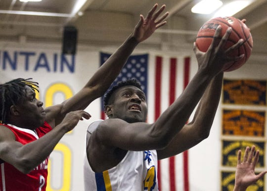 Shadow Mountain's Malik Lamin (44) goes to the basket against Moon Valley's Ty Harper (2) during the first half of their game in Phoenix, Tuesday, Feb .12,  2019.