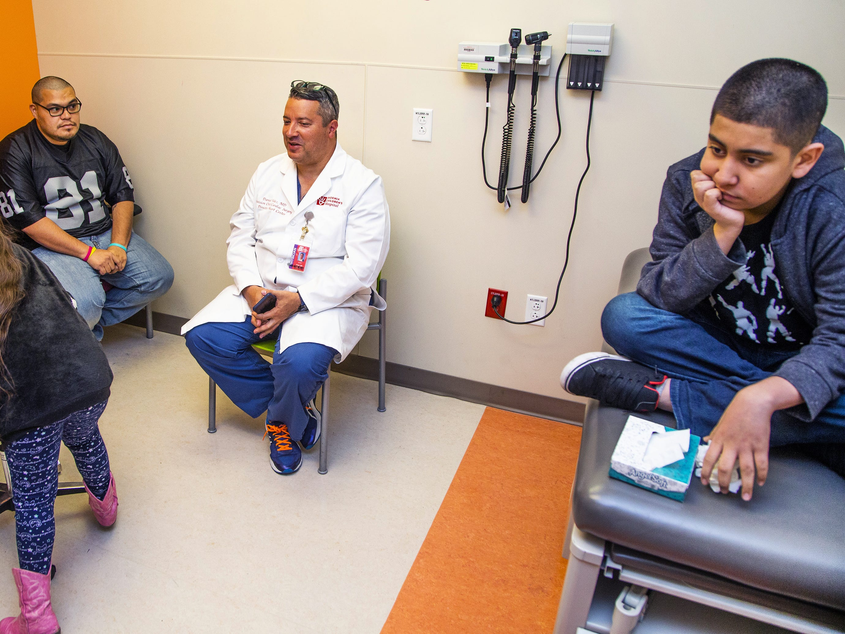 Dr. Daniel Velez speaks with 11-year-old Gabriel Gonzalez, right, and Gabriel's family: sister Aliyah Garcia, 7, mother Anabel Gonzalez, and father Jesus Garcia at Phoenix Children's Hospital, Tuesday.