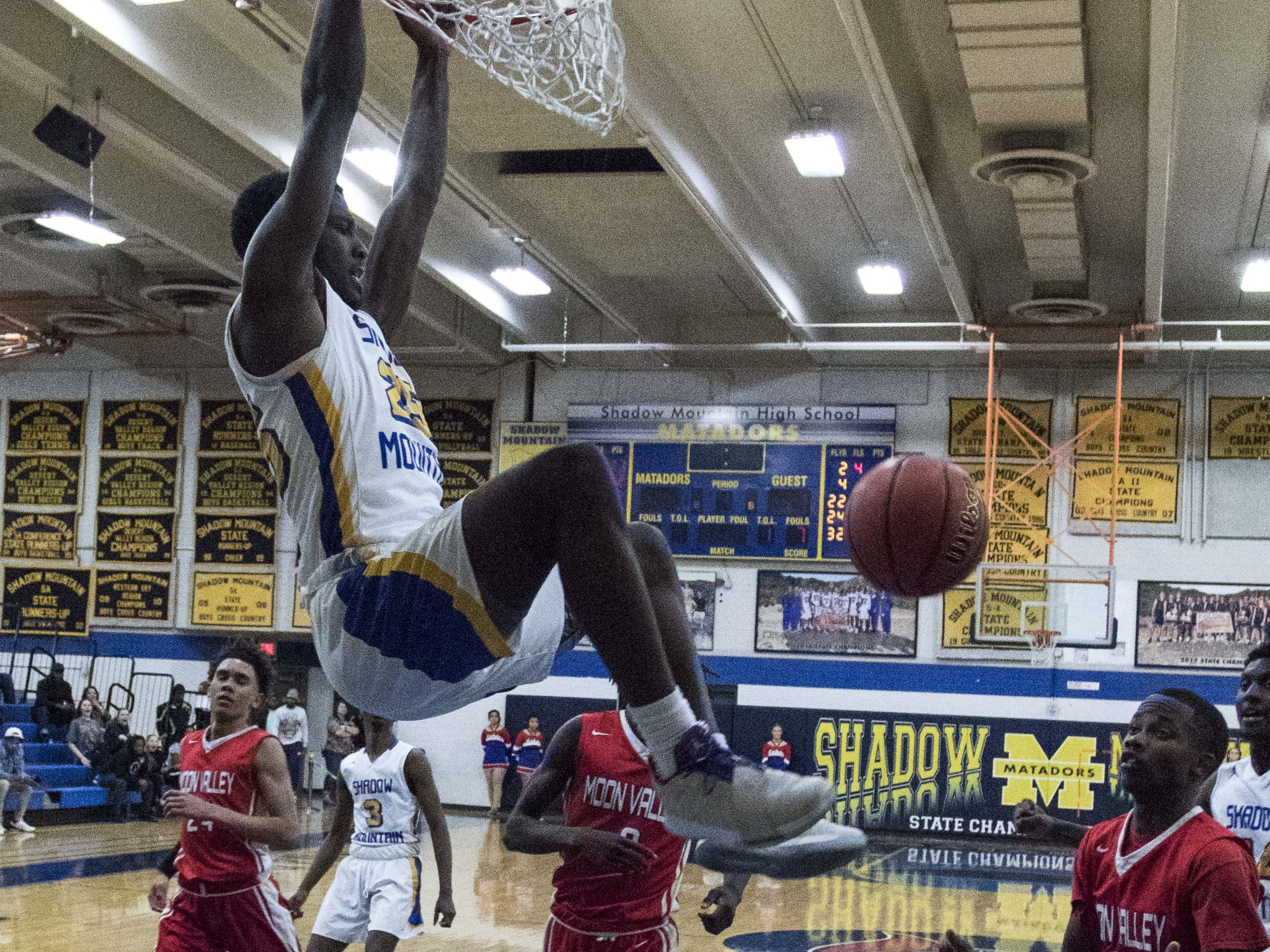 Shadow Mountain's Shemar Morrow (25) throws down a slam dunk over Moon Valley players during the second half of their game in Phoenix, Tuesday, Feb .12,  2019.