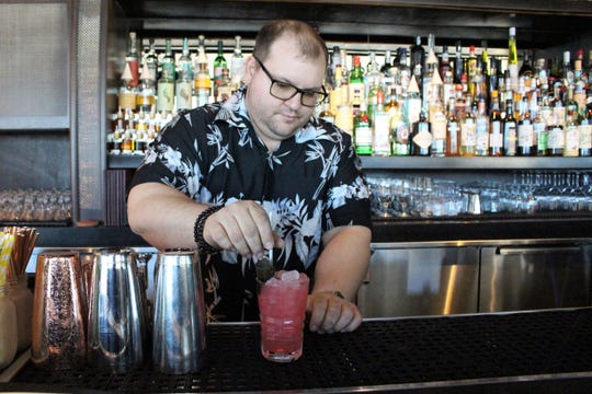 Aaron DeFeo, co-owner of Little Rituals in downtown Phoenix, puts a garnish on the Redcurrant Fix on Tuesday, Feb. 12, 2019.