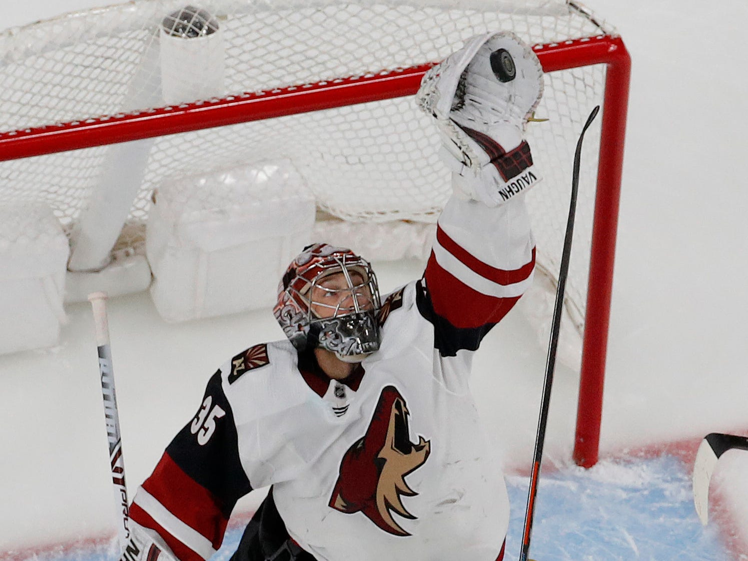 Arizona Coyotes goaltender Darcy Kuemper (35) grabs a puck out of the air beside Vegas Golden Knights left wing Max Pacioretty (67) during the first period of an NHL hockey game Tuesday, Feb. 12, 2019, in Las Vegas. (AP Photo/John Locher)
