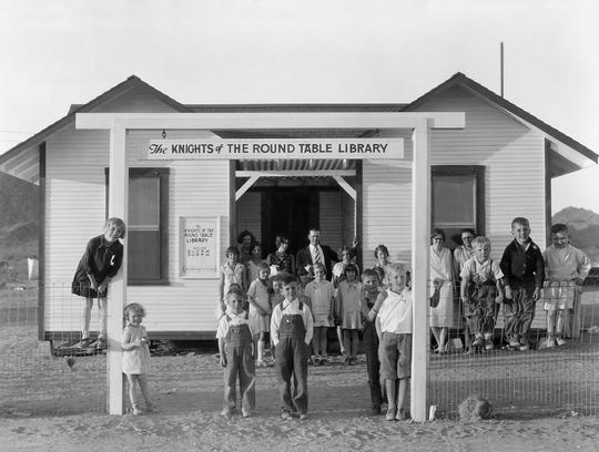 Children stand outside the Desert Mission library built in 1929 through funds raised from The Knights of The Round Table.