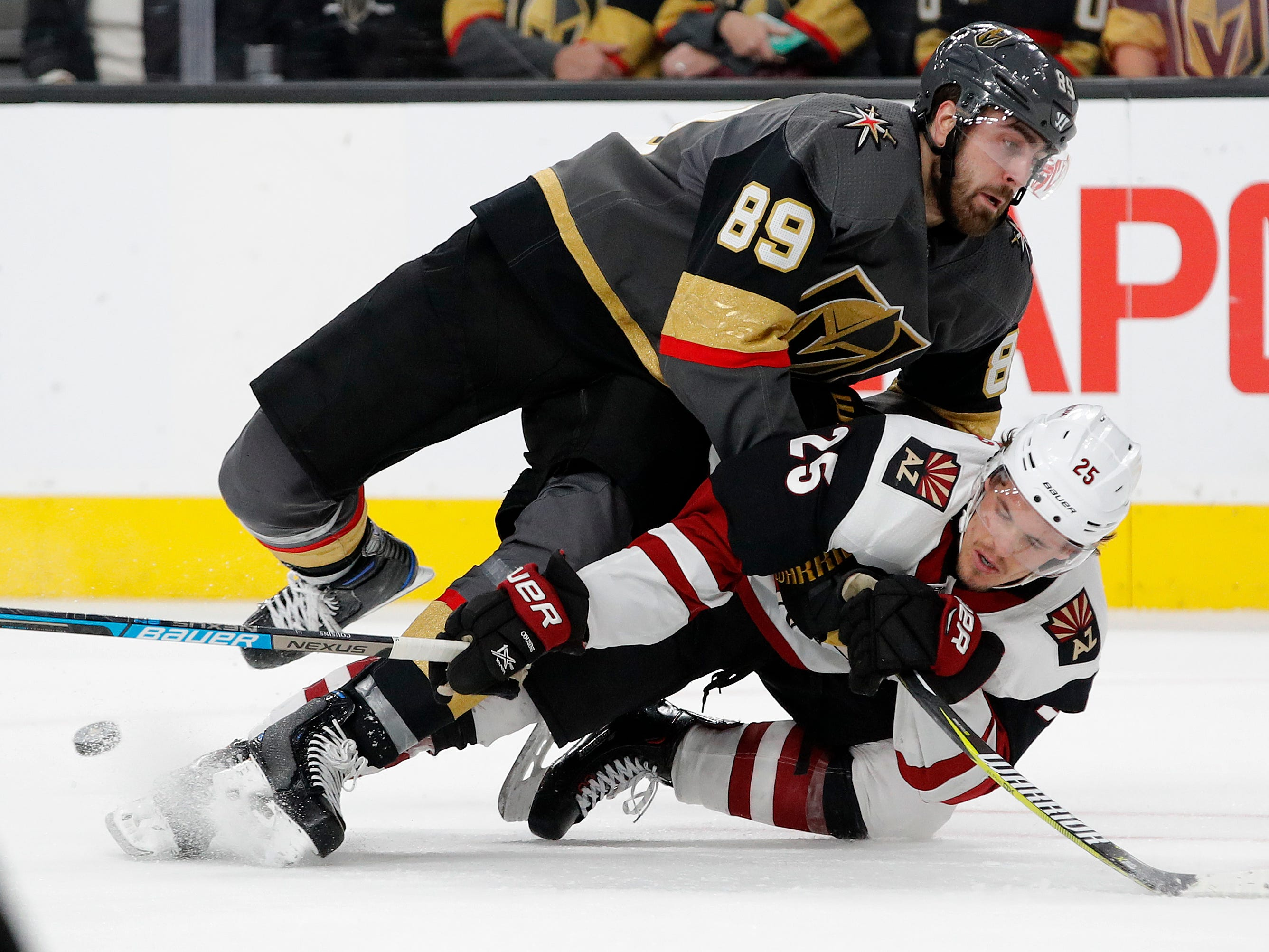 Vegas Golden Knights right wing Alex Tuch (89) falls onto Arizona Coyotes center Nick Cousins (25) during the second period of an NHL hockey game Tuesday, Feb. 12, 2019, in Las Vegas. (AP Photo/John Locher)