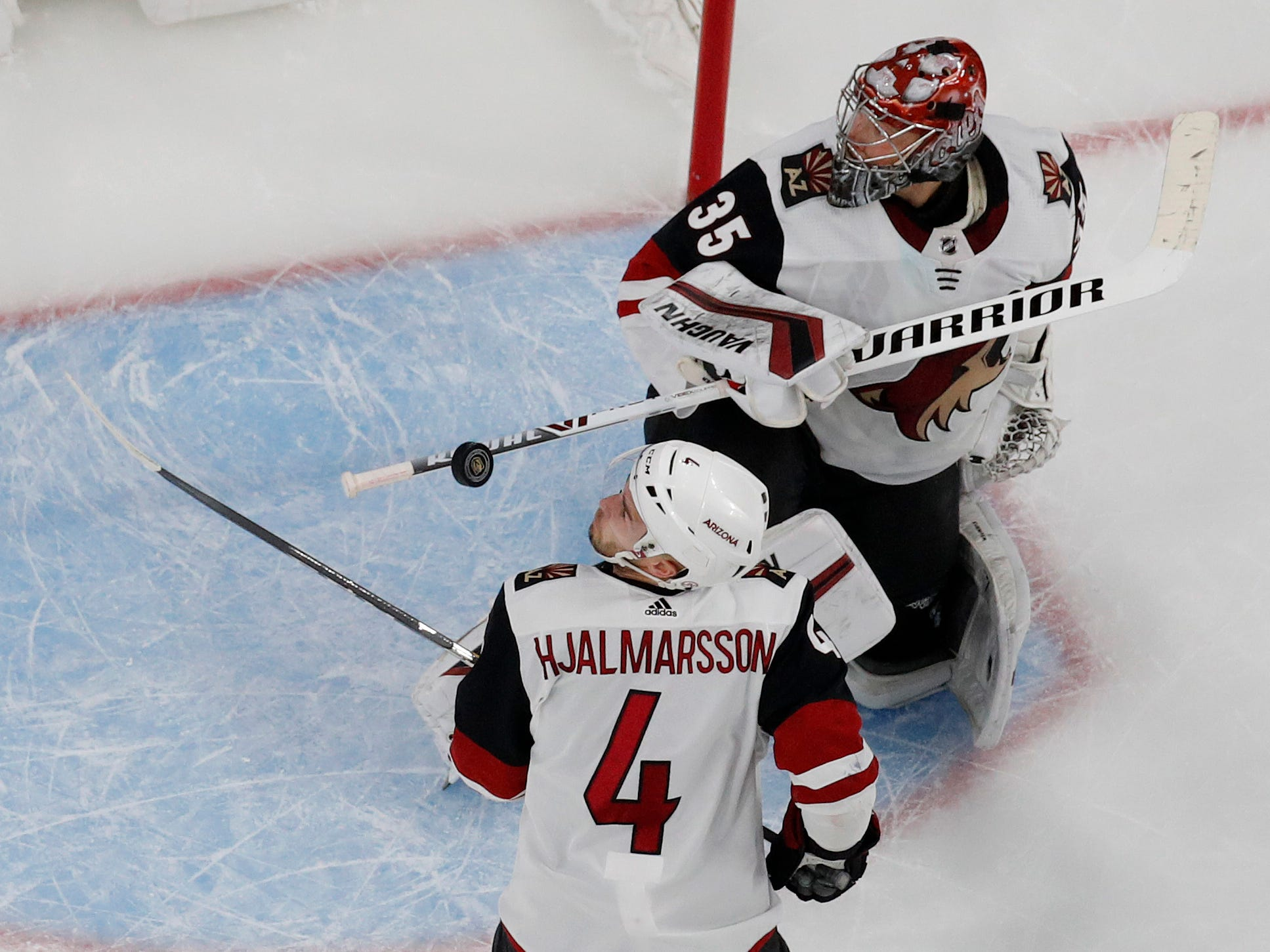 Arizona Coyotes defenseman Niklas Hjalmarsson (4) watches the puck after Arizona Coyotes goaltender Darcy Kuemper (35) made a save during the first period of an NHL hockey game Tuesday, Feb. 12, 2019, in Las Vegas. (AP Photo/John Locher)